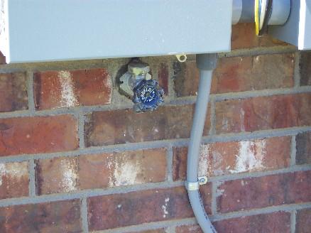 Water faucet directly below main electrical panel - InterNACHI