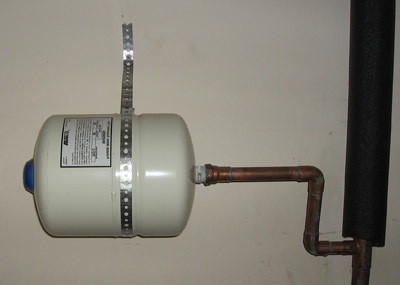 An expansion tank is a metal tank connected to a building's water heating appliance designed to accommodate fluctuations in the volume of a building's hot water