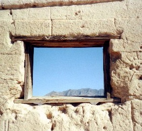A wooden lintel framing a window in an adobe structure