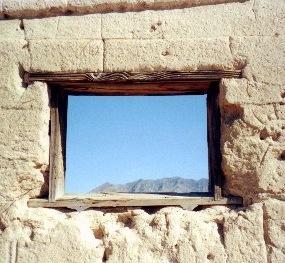 Un dintel de madera enmarca una ventana en una estructura de adobe