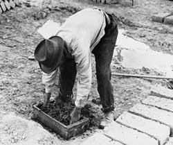 Un hombre moldea los ladrillos de adobe en la moda tradicional.