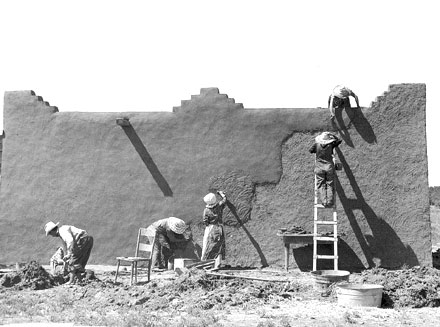 Workers plaster a massive adobe wall.