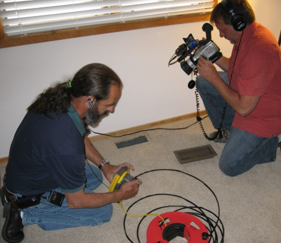 Nick Gromicko films CMI Hank Valenzano as he prepares to inspect a duct.