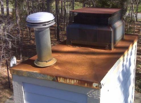 A rusted roof with a rusted chimney vent