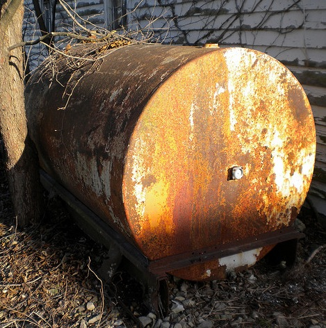 This above-ground oil storage tank has severely rusted and can pose environmental hazards as well as threaten the adjacent structure.
